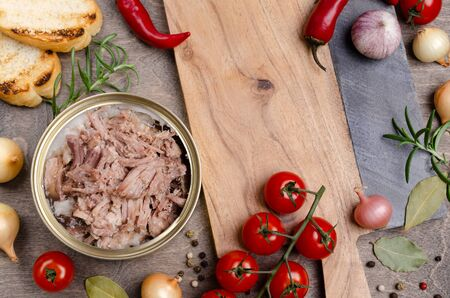 Canned meat in metal with vegetables and spices on a wooden background. Selective focus. Stock Photo