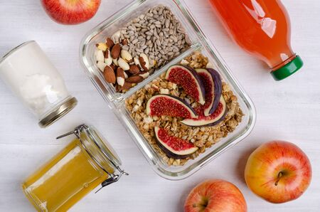 Granola with yogurt, figs and nuts in glass on a wooden background. Selective focus. Archivio Fotografico