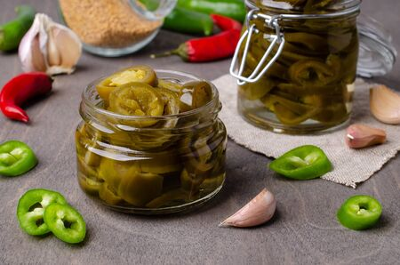 Pickled jalapeno slices in a glass jar on a wooden background. Selective focus. Imagens