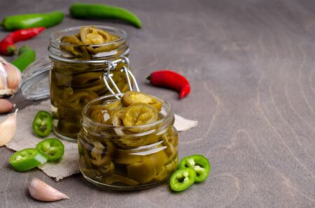 Pickled jalapeno slices in a glass jar on a wooden background. Selective focus. 写真素材