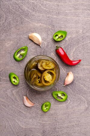 Pickled jalapeno slices in a glass jar on a wooden background. Selective focus. Stock fotó