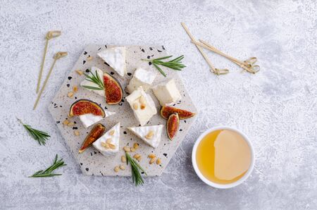 Cheese with white mold with figs, nuts and honey on a slate background. Selective focus. Stock Photo