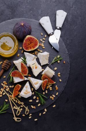 Cheese with white mold with figs, nuts and honey on a slate background. Selective focus. 写真素材