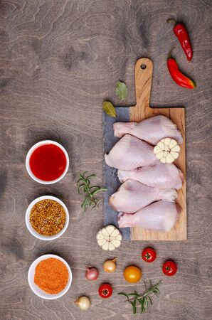 Raw chicken drumsticks with vegetables and spices on a wooden background. Selective focus. Stockfoto