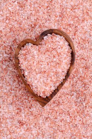 Himalayan pink salt crystals in a wooden bowl. Background of salt crystals. Design concept. Selective focus.