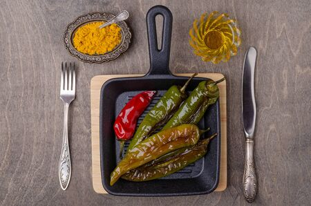 Roasted hot pepper in a serving dish on a wooden background. Selective focus.