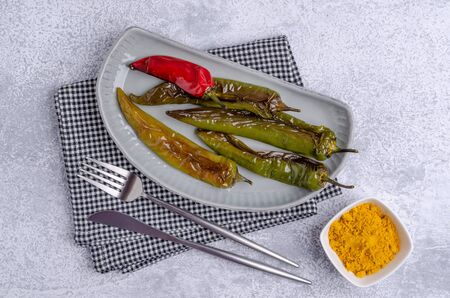Roasted hot pepper in a serving dish on a slate background. Selective focus. 写真素材