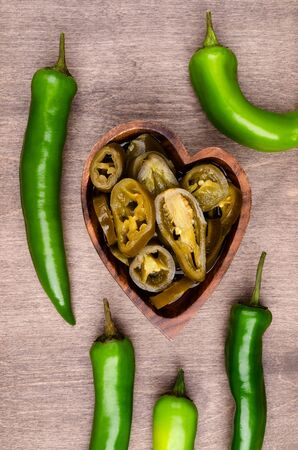 Slices of green pepper pickles in a bowl on a wooden background. Selective focus.