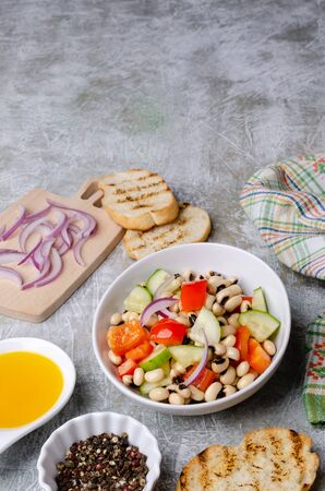 Salad with beans and fresh vegetables in a dish on a slate background. Selective focus.