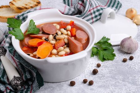 Stewed beans with sausages and vegetables in a ceramic dish. Selective focus.