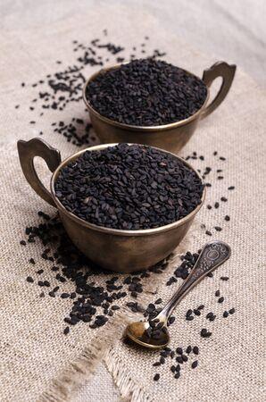 Fresh black sesame in a metal dish on a textile background. Selective focus. 版權商用圖片 - 134691228