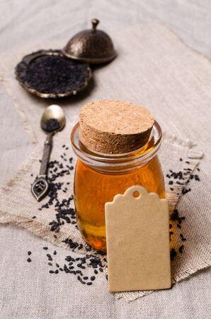 Glass jar with oil. Black sesame seeds. Textile background. Selective focus. 版權商用圖片 - 134691231