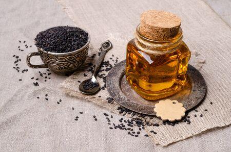 Glass jar with oil. Black sesame seeds. Textile background. Selective focus. 版權商用圖片 - 134691232