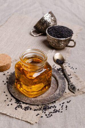 Glass jar with oil. Black sesame seeds. Textile background. Selective focus.