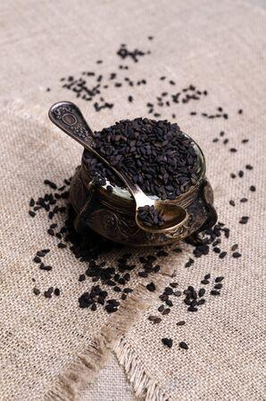 Fresh black sesame in a metal dish on a textile background. Selective focus. 版權商用圖片