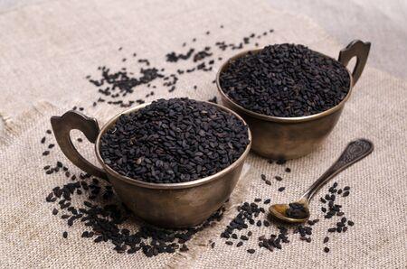 Fresh black sesame in a metal dish on a textile background. Selective focus. 版權商用圖片 - 134691237