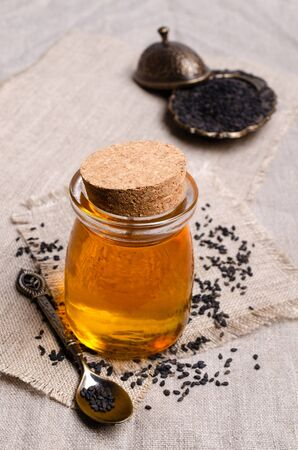Glass jar with oil. Black sesame seeds. Textile background. Selective focus. 版權商用圖片 - 134691240