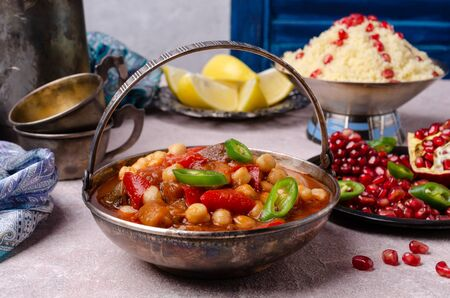 Stewed vegetables with chickpeas and couscous on a slate background. Selective focus.