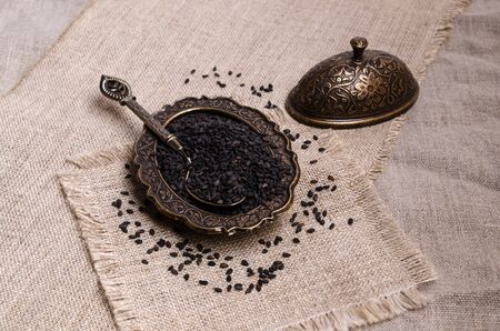 Fresh black sesame in a metal dish on a textile background. Selective focus. Zdjęcie Seryjne