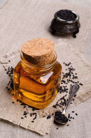 Glass jar with oil. Black sesame seeds. Textile background. Selective focus.