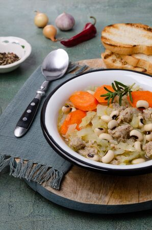 Minced meat with vegetables and beans in a dish on a slate background. Selective focus.