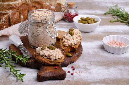Fish pate with capers and rye bread on a wooden background. Selective focus. Foto de archivo
