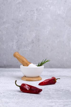 Red pepper with mortar on grey slate background. The concept of cooking spices. Selective focus.