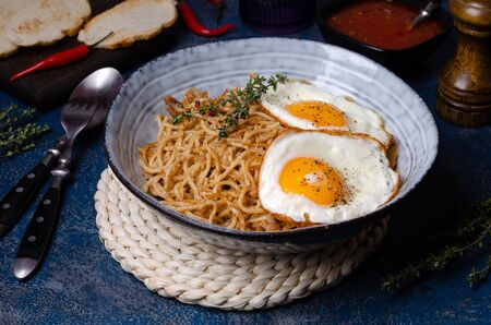 Wholegrain pasta with minced meat and fried eggs. Selective focus.