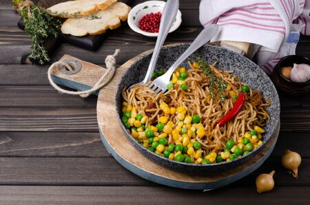 Fried pasta with minced meat and vegetables in a dish on a wooden background. Selective focus. Stock Photo