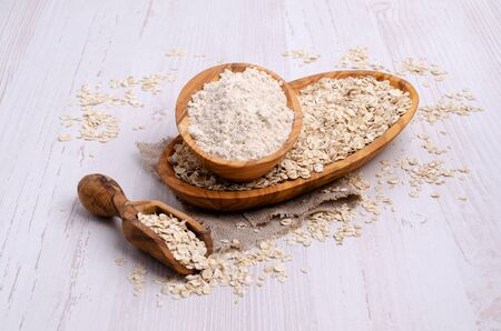 Flour made from oats. Rolled oats. Light wooden background. Selective focus. Stock Photo