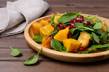 Spinach salad and baked pumpkin with pomegranate seeds in a dish on a wooden background. Selective focus.