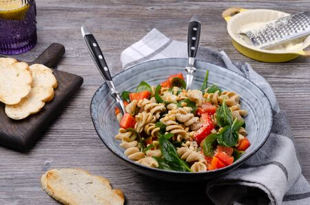 Pasta dorada con verduras, nueces y queso en un plato sobre un fondo de madera. Enfoque selectivo. Foto de archivo