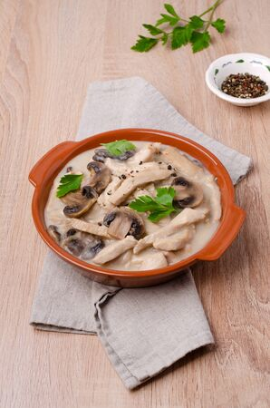 Stewed meat slices with mushrooms in a dish on a wooden background. Selective focus. Stock Photo