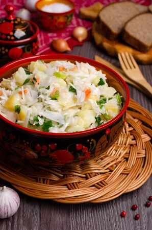 Fermented cabbage salad with vegetables in a dish on a wooden background. Selective focus.