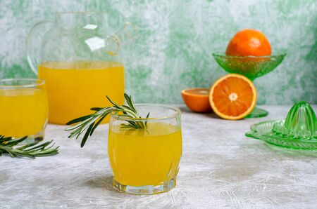 Orange drink with rosemary in the glass on a slate background. Selective focus.