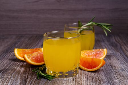 Orange drink with rosemary in glass on a wooden background. Selective focus.
