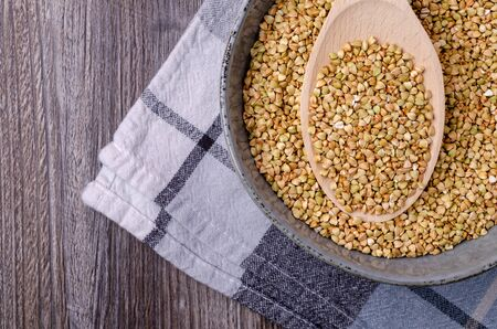 Green buckwheat grains in a dish on a wooden background. The concept of healthy eating. Selective focus.