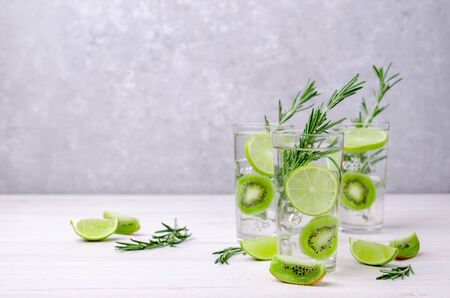 Transparent drink with fruit and rosemary in glass on a light background. Selective focus. Stockfoto