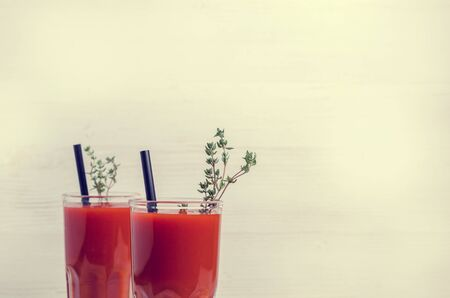 Thick red vegetable juice in glass on a light background. Selective focus.