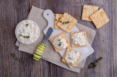 Traditional soft cheese with thyme and crackers on a wooden background. Selective focus. Reklamní fotografie