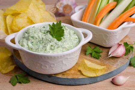 Curd cheese sauce with herbs and vegetables on a wooden background. Selective focus. Imagens - 146907963