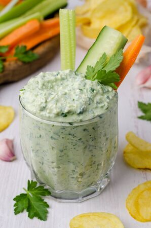 Curd cheese sauce with herbs and vegetables on a wooden background. Selective focus.