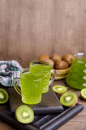 Kiwi drink in glass on a dark wooden background. Selective focus.