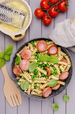 Traditional pasta with sausages and vegetables in a pan on a wooden background. Selective focus.