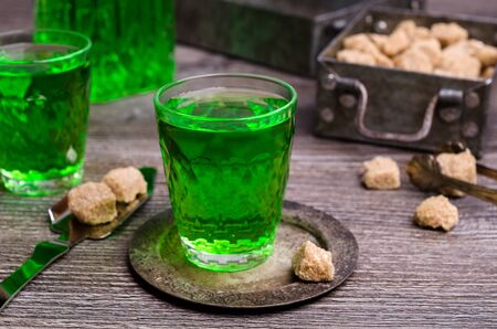 Green liquid in a glass with sugar cubes on a dark wooden background. Selective focus.