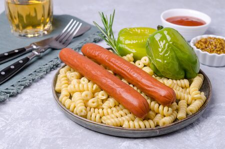 Pasta with sausages and fried peppers in a dish on a slate background. Selective focus. Foto de archivo