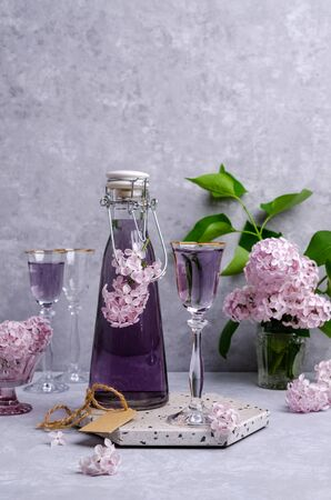 Transparent lilac drink in glass on a slate background. Selective focus.
