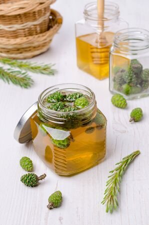 Green cones in yellow syrup in a jar on a wooden background. Selective focus.