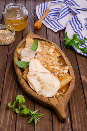 Crepes with pears, nuts and honey honey in a dish on a wooden background. Selective focus.