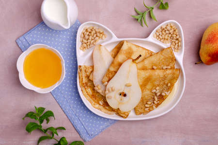 Crepes with pears, nuts and honey in a dish on a slate background. Selective focus. Archivio Fotografico